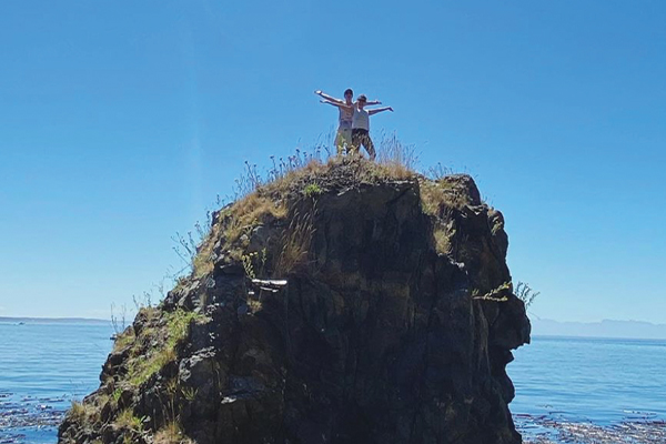 people standing a top of a rock